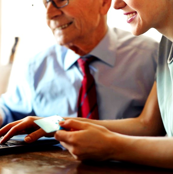 young-woman-helping-senior-man-with-payment-on-internet-3823488 (4)